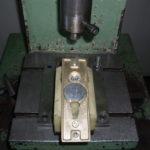 Ajtónyitó gomb préselése a MABISZ által minősített biztonsági veretgarnitúra zárcímébe (zárbetétvédő – pajzs – a cilinderlyuk fölött) a 3,15 tonnás PYTE típusú hidraulikus présgépen – a képen jól látható a nagy keménységű, edzett acélból készített zárbetétvédő elem (biztonsági pajzs), amelyet a 65 tonnás PE-63 A típusú excenter présgépen vágunk ki