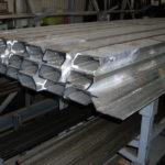 Húzott alumínium szelvények (fent), melyekből darabolással kialakítható a lengőajtó fogantyú és négyszög acélrudak (lent), melyekből az ajtókilincs és ablakkilincs tengelyek készülnek