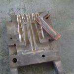 Öntőkokilla fél, a gyártásához szükséges kilincs mintával - jól láthatók az olvadt alumínium megfelelő helyre jutásához szükséges vájatok